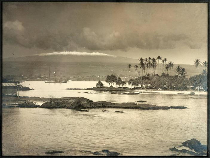 Lovely view of Hilo Bay, Hawaii taken circa 1890. A ship sails in the water, the White Mountains in the background.