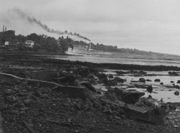 Tsunami wave is sweeping on-shore at the Hilo Sugar Company Mill, with smoke coming out of the smoke stack. Near Hilo Bay on the Big Island of Hawaii. April 1, 1946.