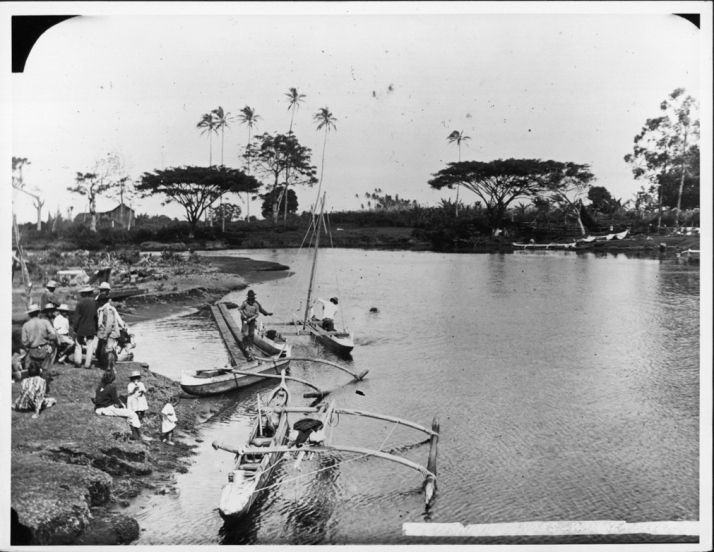 Waiakea River with fishing canoes and people gathered on shore, Hilo, Hawaii Island.